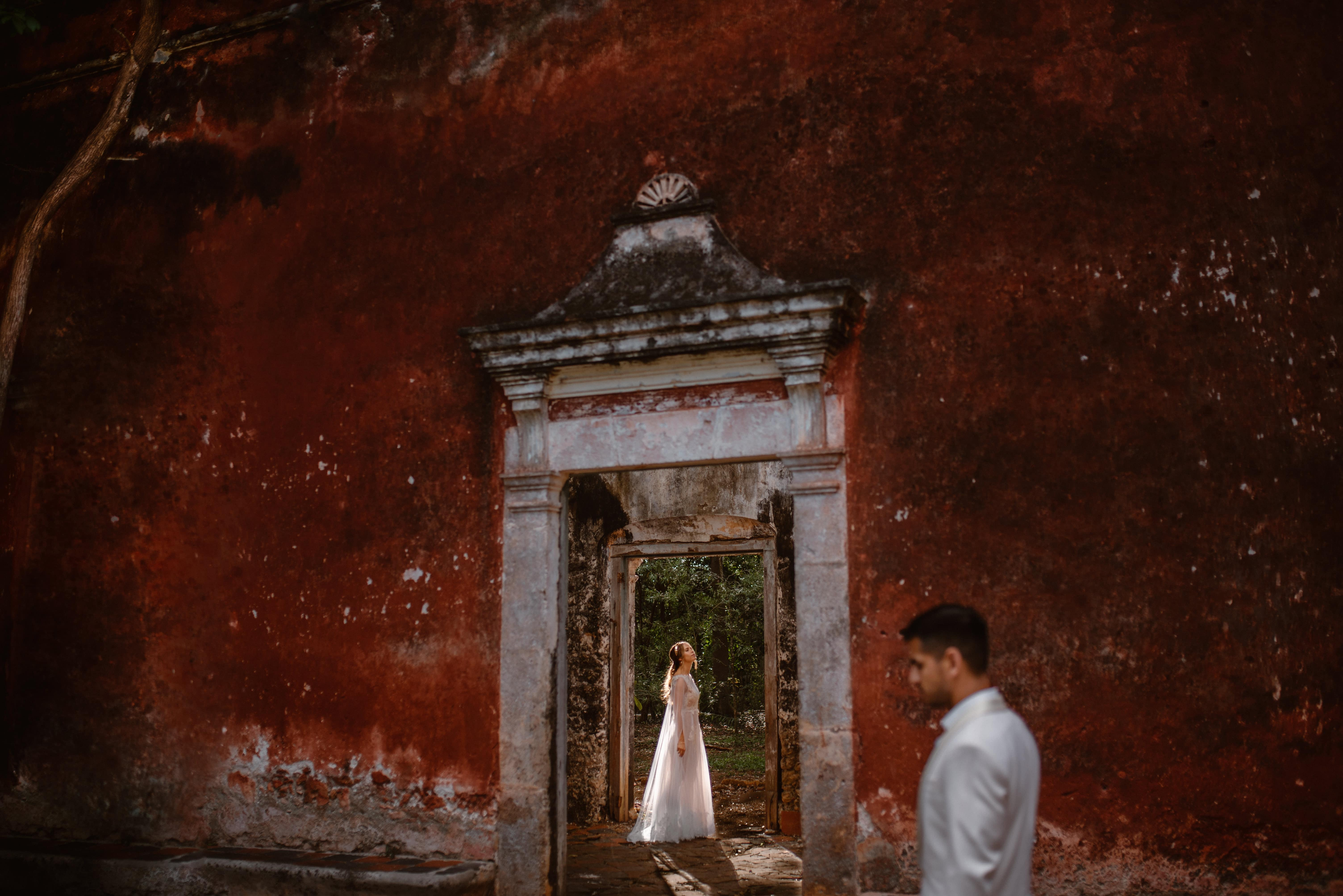 A bride is outlined by the sun standing in the doorway of ruins in Mexico. The groom is blurred in the foreground, standing against a large textured red wall. Eloping in Mexico is one of the best location to elope.